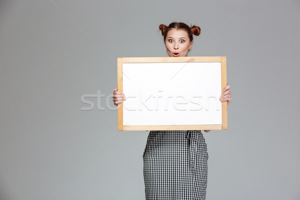 Amusing surprised young woman holding blank whiteboard  Stock photo © deandrobot