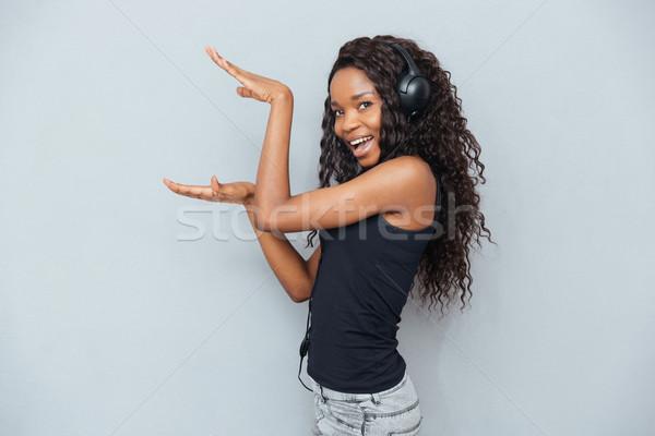 Happy afro american woman in headphones  Stock photo © deandrobot