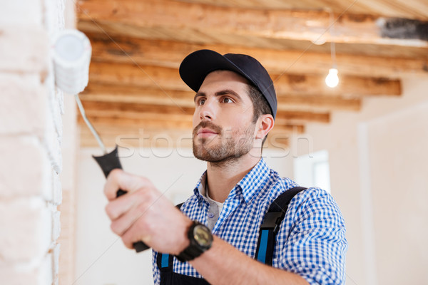 Close-up portrait of a builder worker painting wall indoors Stock photo © deandrobot