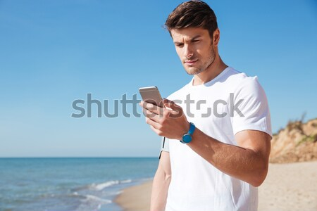 Cheerful young sportsman using smartphone on the beach Stock photo © deandrobot