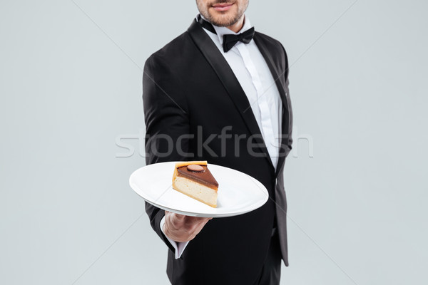 Butler in tuxedo holding plate with piece of cake Stock photo © deandrobot