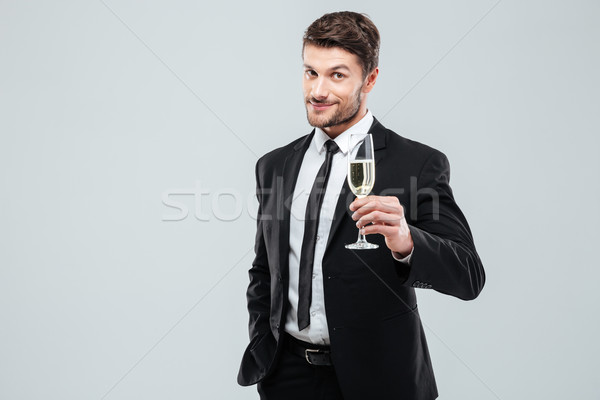 Businessman in suit and tie cheers with glass of champagne Stock photo © deandrobot
