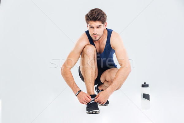 Handsome young sportsman tie shoelaces on his sneakers Stock photo © deandrobot