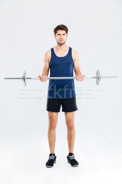 Concentrated young sportsman doing exercises for biceps using barbell Stock photo © deandrobot