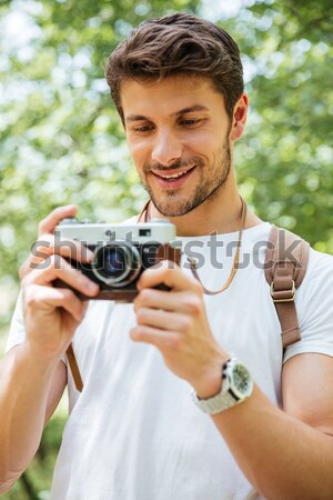 Smiling man with backpack taking photos using vintage camera outdoors Stock photo © deandrobot