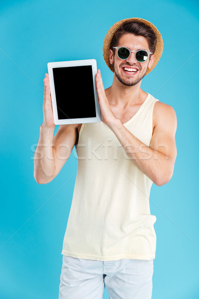 Happy attractive young man holding blank screen tablet Stock photo © deandrobot