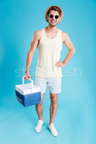 Cheerful young man standing and holding cooler bag Stock photo © deandrobot