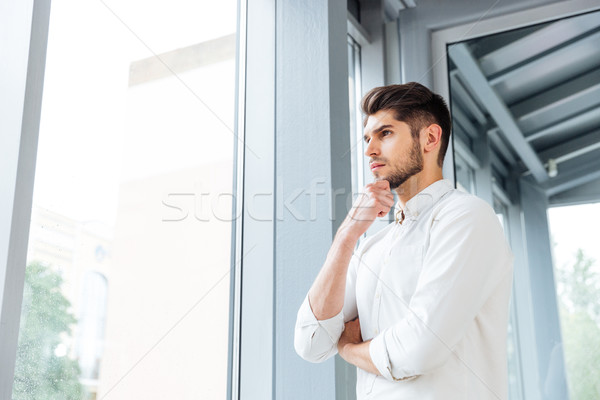Man standing near the window and thinking Stock photo © deandrobot