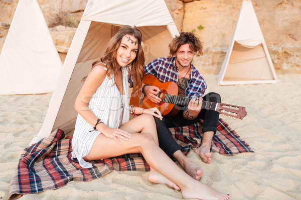 Couple sitting and playing guitar in teepee on the beach Stock photo © deandrobot