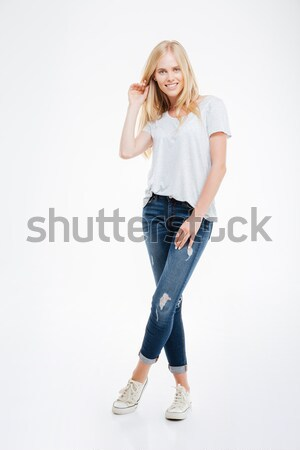 Full length portrait of a woman standing with legs crossed Stock photo © deandrobot