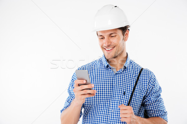 Smiling young man builder in hard hat using mobile phone Stock photo © deandrobot