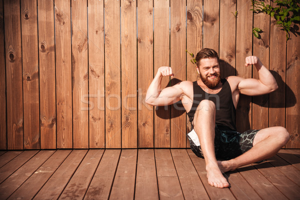 Handsome young smiling man sitting and showing muscles Stock photo © deandrobot