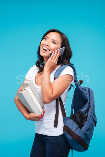 Vietnamese girl holding backpack and books talking on the phone Stock photo © deandrobot