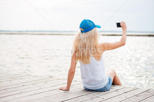 Fiatal szőke nő lány elvesz telefon fából készült Stock fotó © deandrobot