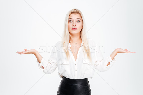 Confused thoughtful young businesswoman holding copyspace on both palms Stock photo © deandrobot