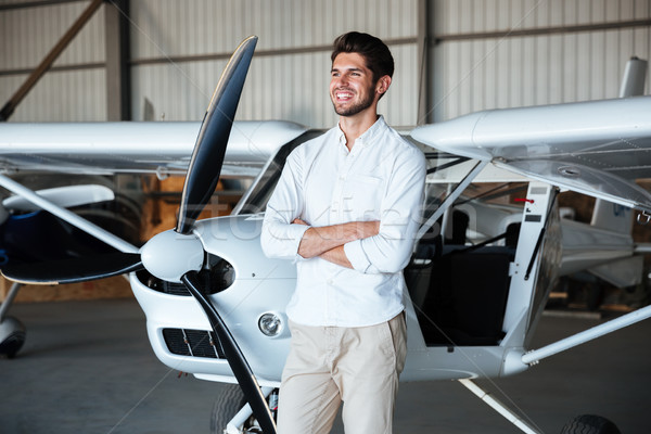 Cheerful young man standing near the plane Stock photo © deandrobot