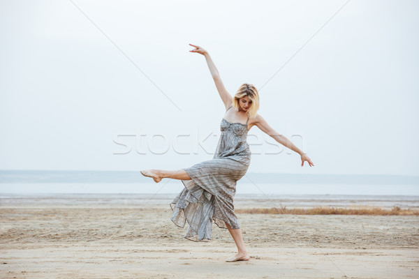 Woman dancer in long dress dancing barefoot on the beach Stock photo © deandrobot