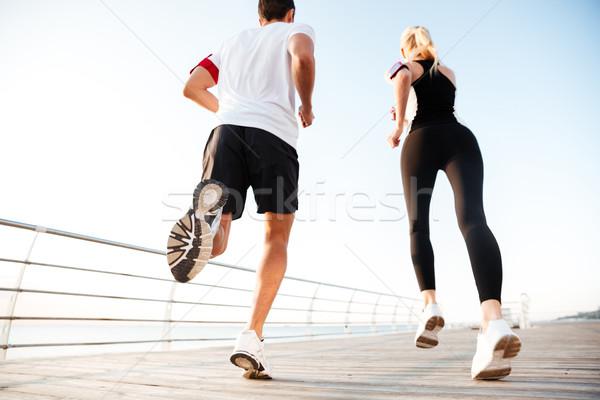 Vue arrière jogging plage pier matin Photo stock © deandrobot