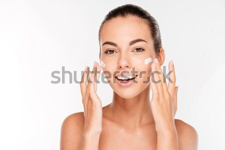 Beautiful young woman applying cosmetic cream treatment on her face Stock photo © deandrobot
