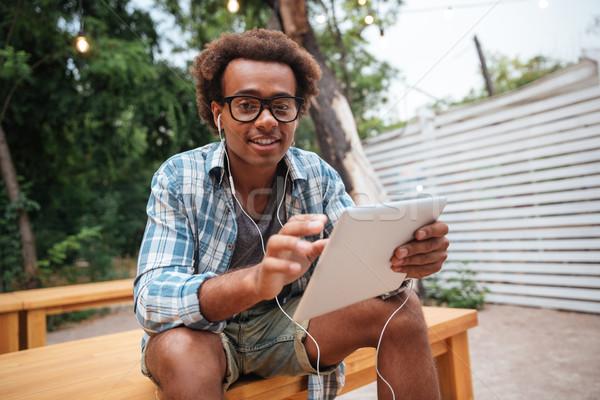Mosolyog férfi fülhallgató zenét hallgat tabletta kint Stock fotó © deandrobot