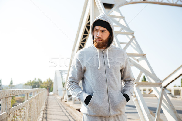 Young sportive man in hood walking along urban bridge Stock photo © deandrobot