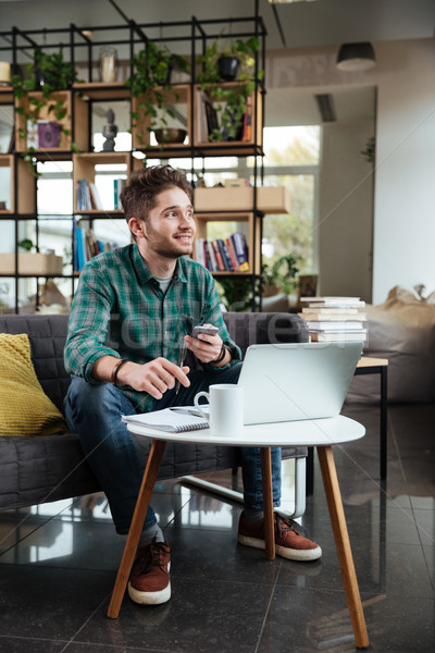 Vertical image of handsome man writing something Stock photo © deandrobot