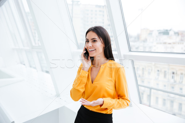 Business woman standing near the window with phone Stock photo © deandrobot