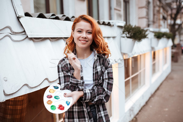 Happy lady painter with red hair walking on the street Stock photo © deandrobot
