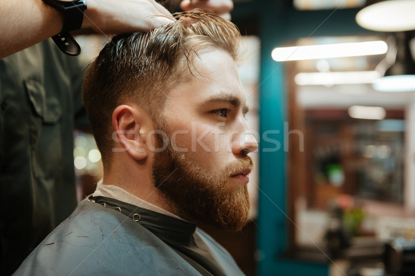 Young man getting haircut by hairdresser with scissors Stock photo © deandrobot