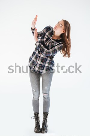 Scared shocked young woman standing and protecting by hands Stock photo © deandrobot