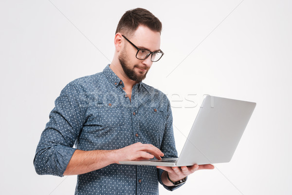 Concentrated young bearded man using laptop Stock photo © deandrobot