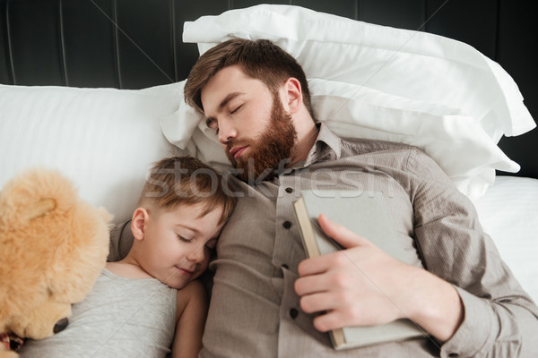 Boy sleeping near toy with his bearded father holding book. Stock photo © deandrobot