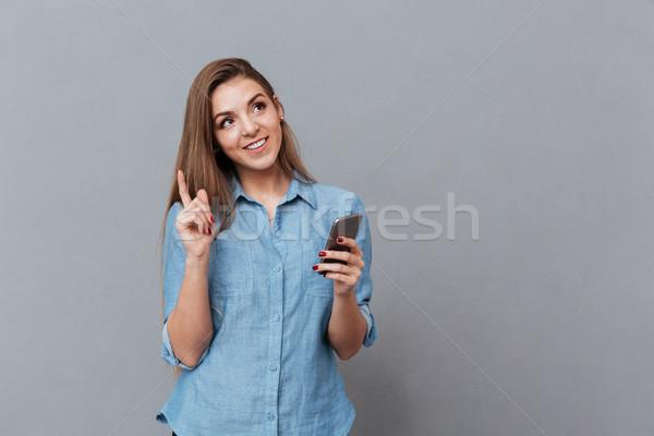 улыбаясь задумчивый женщину рубашку телефон Идея Сток-фото © deandrobot