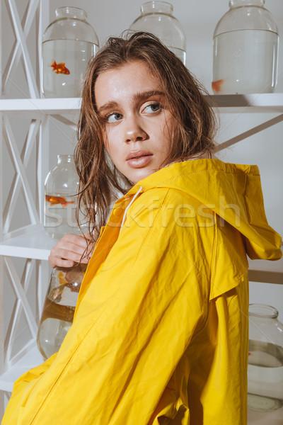 Assustado mulher amarelo capa de chuva ocultação jarra Foto stock © deandrobot