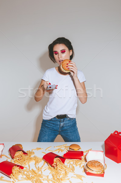Attractive young woman eating hamburger and using cell phone Stock photo © deandrobot