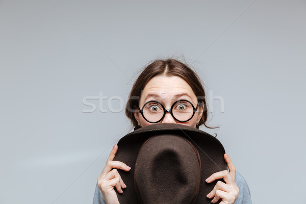 Surprised Female nerd looking behind the hat Stock photo © deandrobot