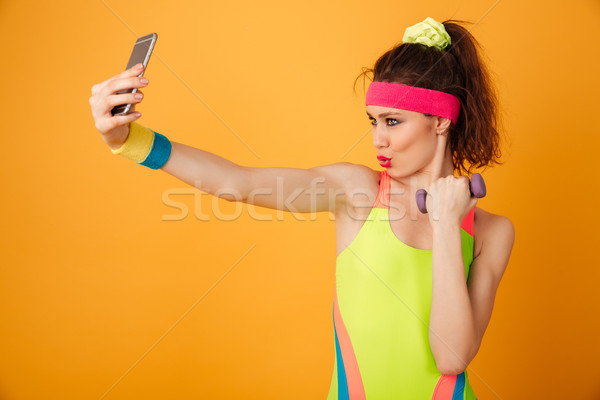 Happy playful young woman athlete holding dumbbell and taking selfie Stock photo © deandrobot
