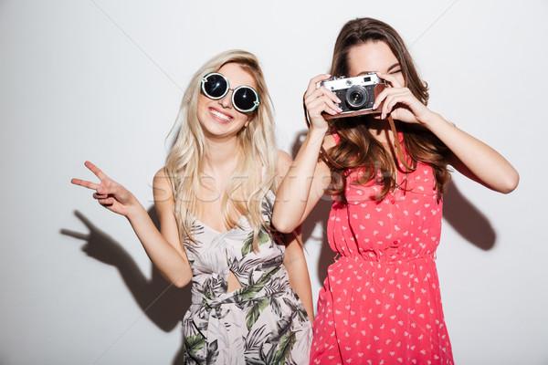 Two smiling stylish women with retro camera Stock photo © deandrobot