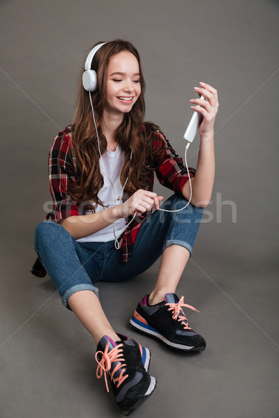 Cheerful in headphones sitting and listening to music from smartphone Stock photo © deandrobot