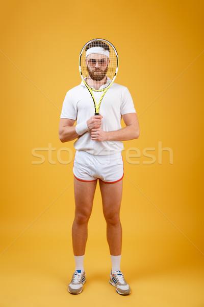 Vertical image of sportsman looking through tennis racquet Stock photo © deandrobot