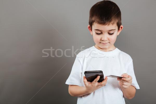 Foto stock: Bonitinho · pequeno · menino · celular · cartão · de · crédito · cinza