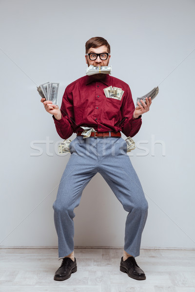 Vertical image of Male nerd with many money Stock photo © deandrobot