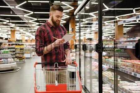 Knap jonge man permanente supermarkt praten telefoon Stockfoto © deandrobot