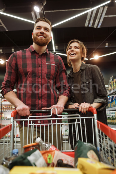 Young loving couple in supermarket with shopping trolley Stock photo © deandrobot
