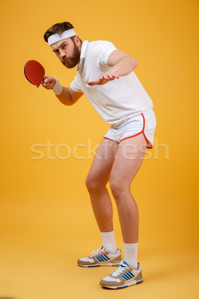 Handsome young sportsman holding racket for table tennis. Stock photo © deandrobot