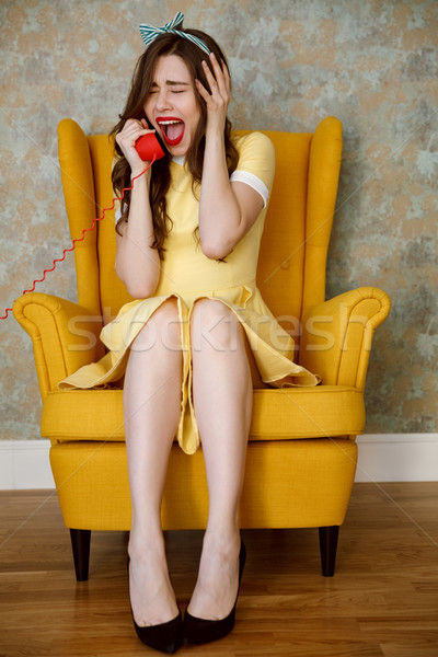 Vertical image of crying woman on armchair talking at handset Stock photo © deandrobot