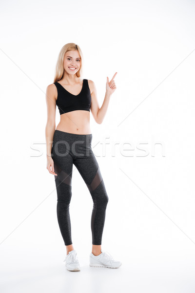 Cheerful pretty fitness lady pointing to copyspace. Stock photo © deandrobot