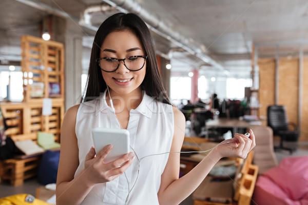Stockfoto: Glimlachende · vrouw · permanente · luisteren · naar · muziek · mobiele · telefoon · glimlachend · asian
