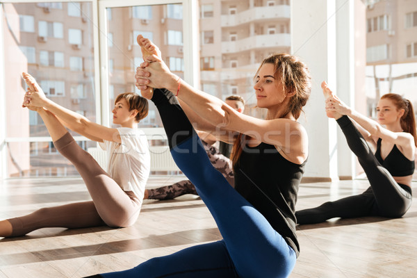 Group of people sitting and stretching legs in yoga studio Stock photo © deandrobot