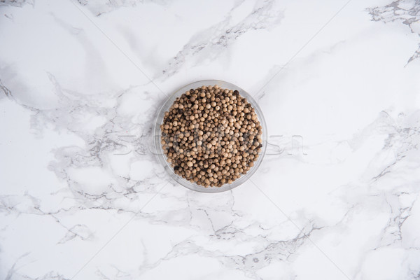Top view of white peppercorns seeds iin bowl on white Stock photo © deandrobot